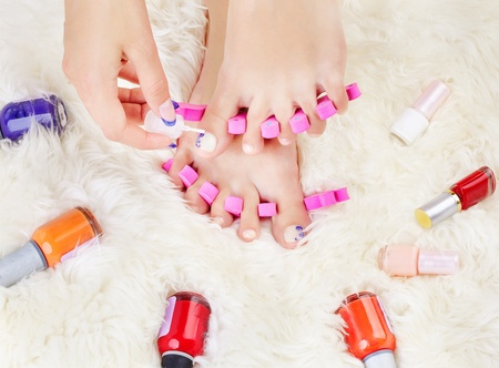 body part shot of healthy woman's feet in pedicure toe separators. hand is putting polish on toenail Stock Photo - 10810700