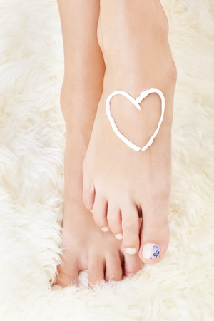 foot model: body part shot of beautiful healthy young womans legs. heart is drawn with white care cream on foot