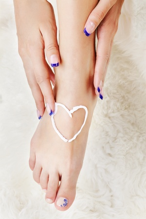 body part shot of beautiful healthy young womans leg and manicured hands. heart is drawn with white care cream on pedicured foot photo