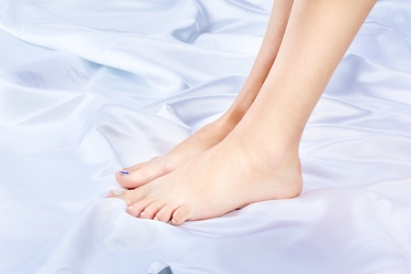 body part shot of beautiful healthy young womans legs on silk cloth photo