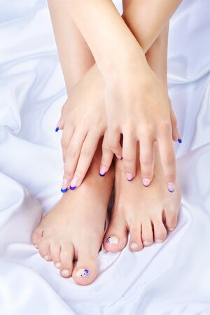 body part shot of beautiful healthy young womans hands and legs with manicured fingers and pedicured toes on silk cloth photo