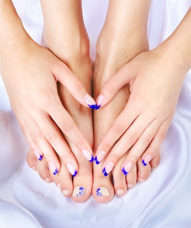 pedicura: disparo de parte de cuerpo de la de hermosa joven mujer sana manos y piernas con cuidado los dedos y dedos pedicured sobre tela de seda