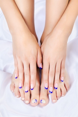human toe: body part shot of beautiful healthy young womans hands and legs with manicured fingers and pedicured toes on silk cloth