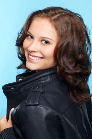 portrait of beautiful young brunette woman in black leather jacket on blue