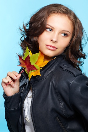 european people: portrait of beautiful young brunette woman in black leather jacket with autumn maple leaves