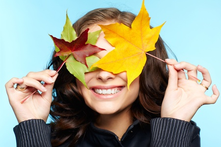 yellow jacket: portrait of beautiful young brunette woman in black leather jacket hiding eyes behind autumn maple leaves