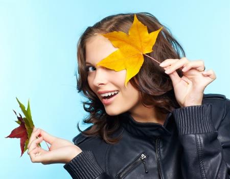 chaqueta de cuero: Retrato de la bella joven Morena en la chaqueta de cuero negro con Arce oto�o hojas Foto de archivo