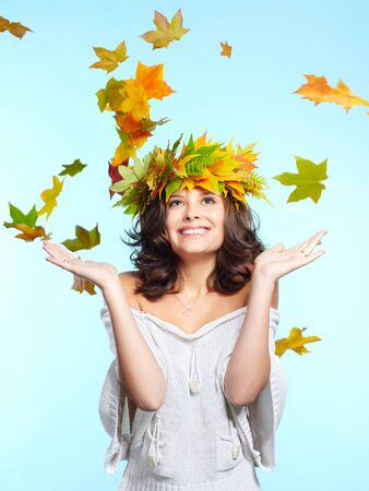 portrait of beautiful young brunette woman in garland of autumn maple and fern leaves spreading hands to falling leaves photo