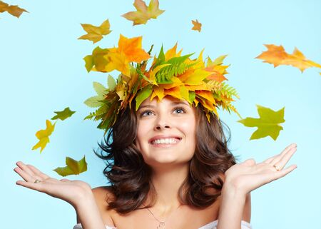 portrait of beautiful happy young brunette woman in garland of autumn maple and fern leaves photo