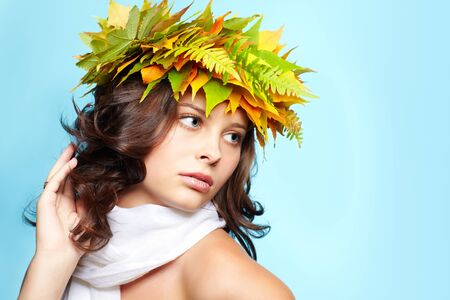 portrait of beautiful young brunette woman in garland of autumn maple and fern leaves photo