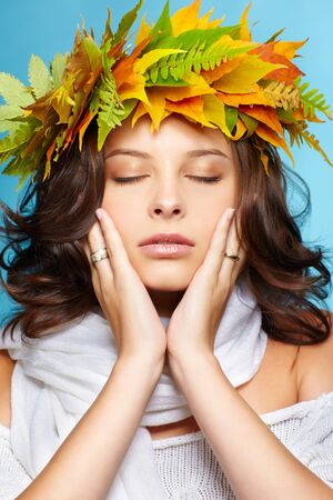 closed eye: portrait of beautiful young brunette woman with closed eyes in garland of autumn maple and fern leaves