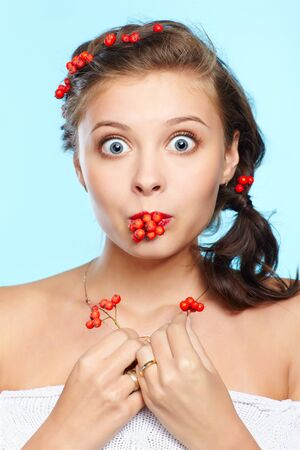 expression portrait of surprised beautiful young brunette woman with red ashberries on blue photo