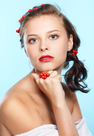 portrait of beautiful young brunette woman with red ashberries on blue photo