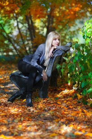 Beautiful young woman sitting on a bench in autumn park photo