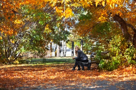 Beautiful young woman sitting on a bench in autumn park Stock Photo - 11178464