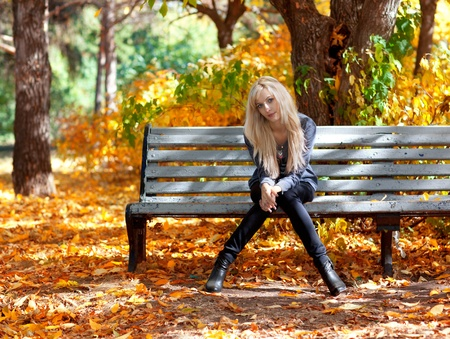 court shoes: Beautiful young woman sitting on a bench in autumn park Stock Photo