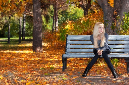 Beautiful young woman sitting on a bench in autumn park Stock Photo - 11178470