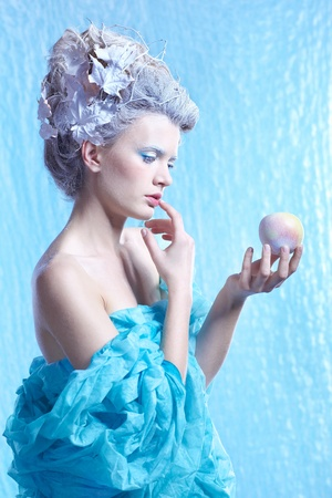 fantasy portrait of beautiful young woman imaging ice fairy with frozen apple on blue photo