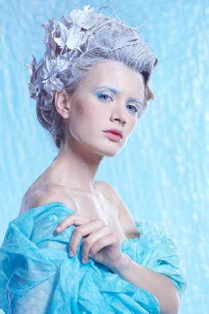 fantasy portrait of beautiful young woman imaging ice fairy on frozen blue photo