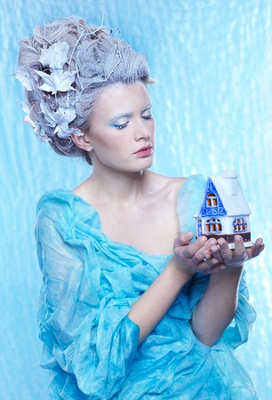 fantasy portrait of beautiful young woman imaging ice fairy on frozen blue with toy house photo