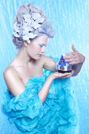 maquillaje de fantasia: retrato de la fantasía hermosa hada de hielo joven de imágenes en color azul congelado con casa de juguete