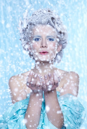 fantasy portrait of beautiful young woman imaging ice fairy on frozen blue blowing snow from hands photo