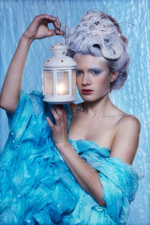 magic lamp: fantasy portrait of beautiful young woman imaging ice fairy on frozen blue with lantern
