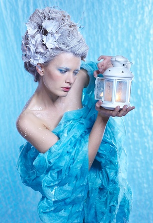 fantasy portrait of beautiful young woman imaging ice fairy on frozen blue with lantern photo