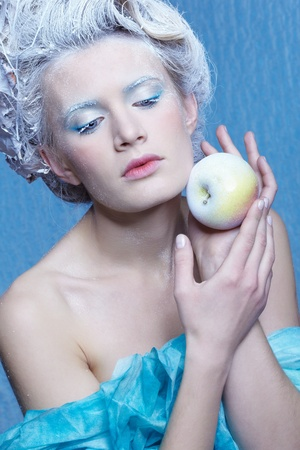 fantasy portrait of beautiful young woman imaging ice fairy on frozen blue with apple photo