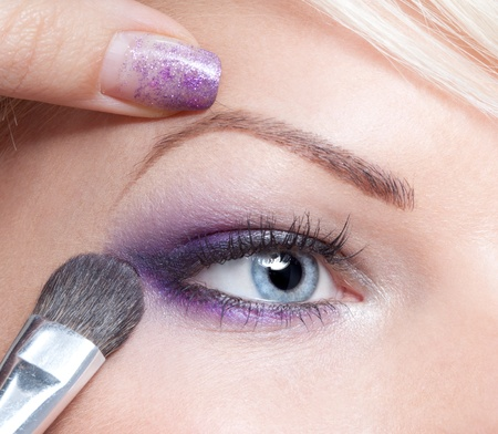 Makeup artist applying beautiful make up eyeshadow photo