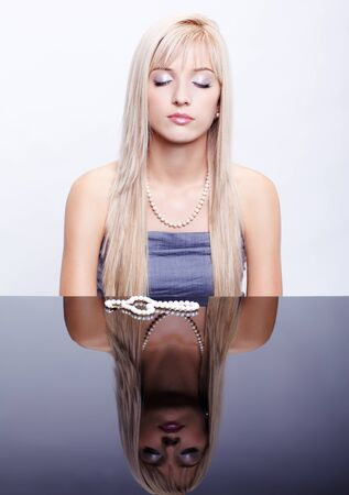 shut: portrait of young beautiful long-haired blonde woman with eyes shut sitting at mirror table with pair of pearl beads