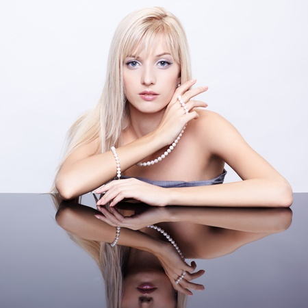 string of pearls: portrait of young beautiful blonde woman sitting at mirror table with string of pearls