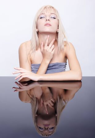 portrait of young beautiful long-haired blonde woman sitting at reflecting table photo