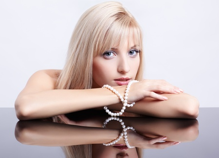 string of pearls: portrait of young beautiful blonde woman sitting with pearl necklace at reflecting table