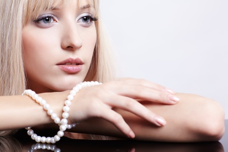fashion jewelry: portrait of young beautiful long-haired blonde woman with pearl beads Stock Photo