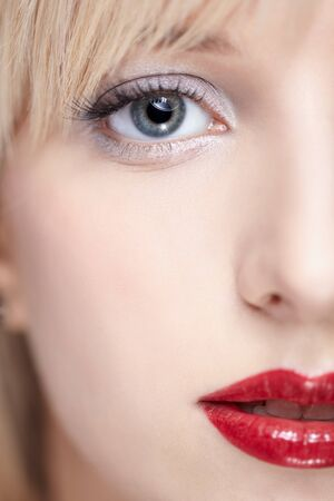 close-up half face portrait of beautiful woman with with fresh skin and bright red lips photo