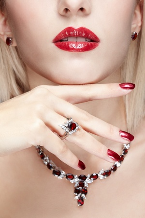 close-up body part portrait of beautiful woman with healthy skin, red manicure and jewellery photo