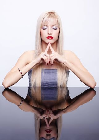 shut: portrait of young beautiful long-haired blonde woman with eyes shut meditating at mirror table in bracelet and ring Stock Photo