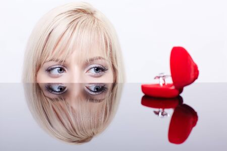 portrait of young beautiful blonde woman behind mirror table looking at red ring box photo