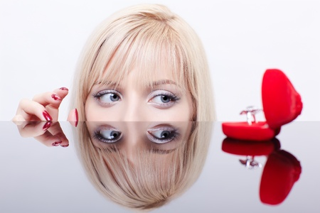 mirror face: portrait of young beautiful blonde woman behind mirror table stretching manicured fingers to red ring box