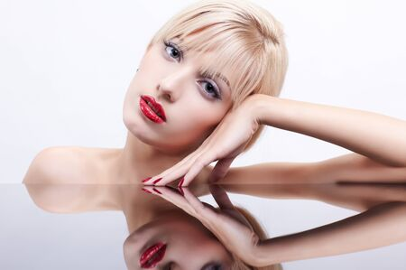 portrait of young beautiful blonde woman with manicured fingers sitting at reflecting table photo