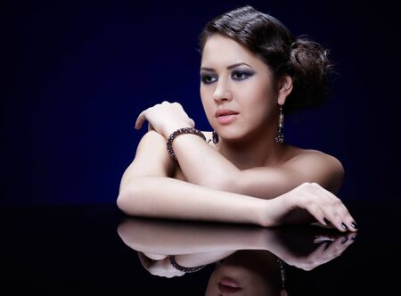 portrait of young beautiful brunette woman in jewelry at reflecting table photo