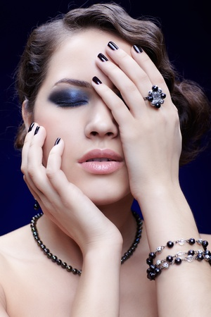 portrait of young beautiful brunette woman in bracelet, necklace and ring with manicured fingers touching her face photo