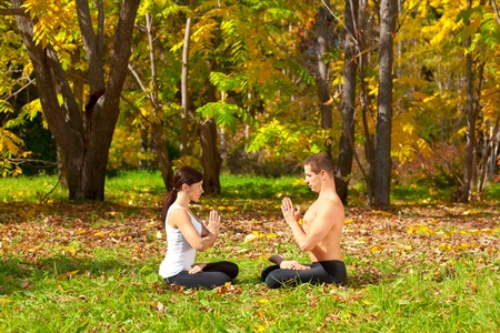 An attractive  man and woman practice Yoga padmasana pose in forest photo