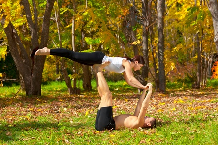 An attractive  man and woman practice tantra yoga in forest Stock Photo
