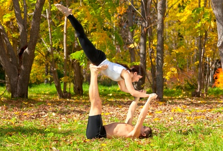 tantra: An attractive  man and woman practice tantra yoga in forest Stock Photo