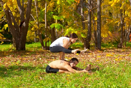 Man and woman practice Yoga tittibhasana on pashchimottanasane pose in forest photo