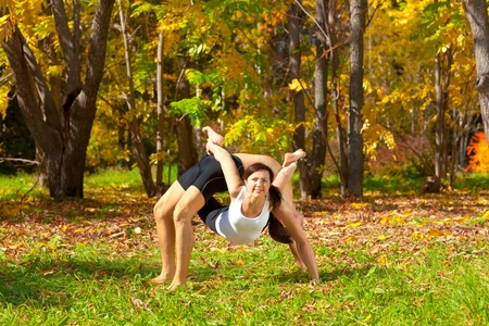 Man and woman practice Yoga dhanurasana under urdhva dhanurasana pose in forest photo