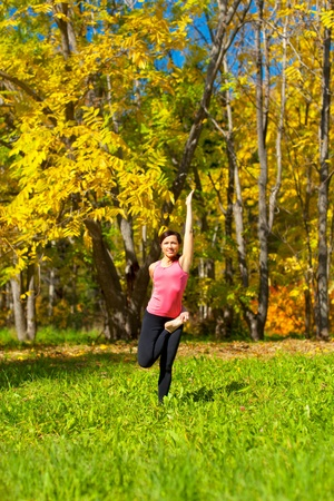 Woman exercises in the autumn forest yoga Ardha baddha padmottanasana pose photo