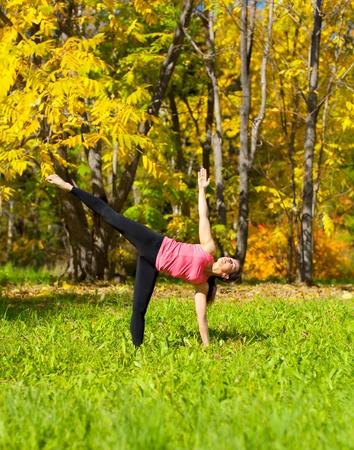 chandrasana: Woman exercises in the autumn forest yoga Ardha chandrasana pose